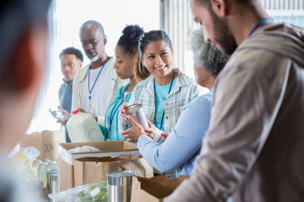 Diverse group of people volunteer in food bank stock photo