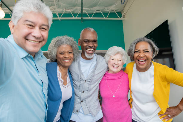 Diverse group of seniors smiling together with arms around each other stock photo