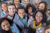 A large group of cheerful diverse young adults looking up and smiling at the camera. The group includes male and female African American, Hispanic and Caucasian ethnicities.
