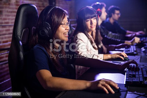 Young college students playing esports at computer stations