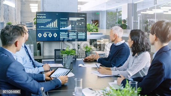 istock Diverse Group of Successful Business People in the Conference Room, Discuss  Company's Growth Shown on the Wall TV Illustrated by Charts and Statistics. 921054690