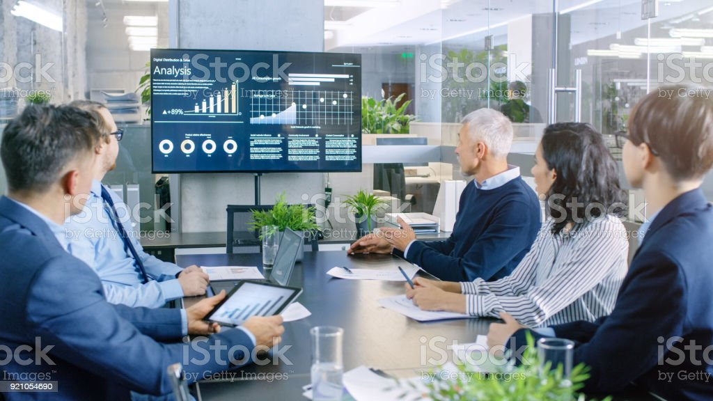Diverse Group of Successful Business People in the Conference Room, Discuss  Company's Growth Shown on the Wall TV Illustrated by Charts and Statistics. stock photo
