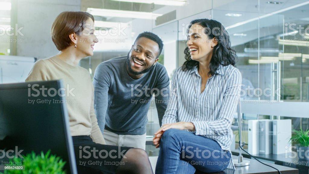 Groupe diversifié de talentueux jeunes professionnels bavarder, plaisanter et s'amuser sur une pause-café. Jeunes élégants bureau moderne. - Photo de A la mode libre de droits