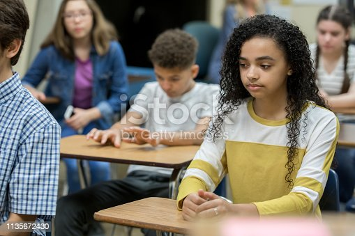 Diverse group of teenage high school students sitting at desks during detention, looking bored and depressed