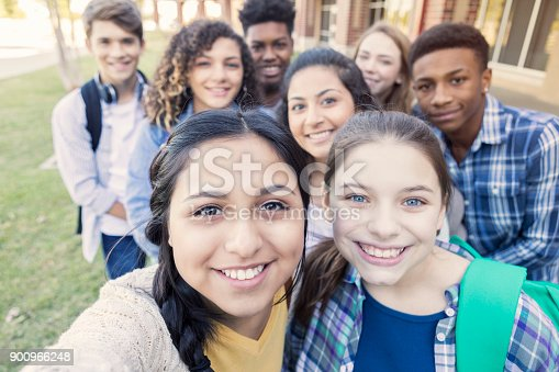 istock Diverse group of teens looking at camera taking selfie at high school 900966248