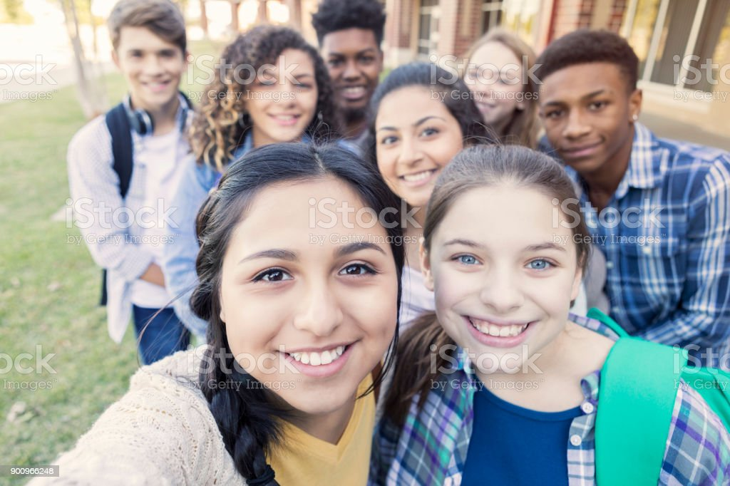Diverse group of teens looking at camera taking selfie at high school stock photo