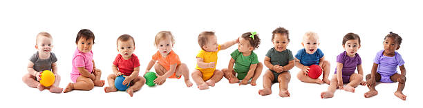 Diverse group of ten babies playing An image of babies and toddlers of various ethnicities wearing colorful onesies and sitting side by side in a long line. baby human age stock pictures, royalty-free photos & images