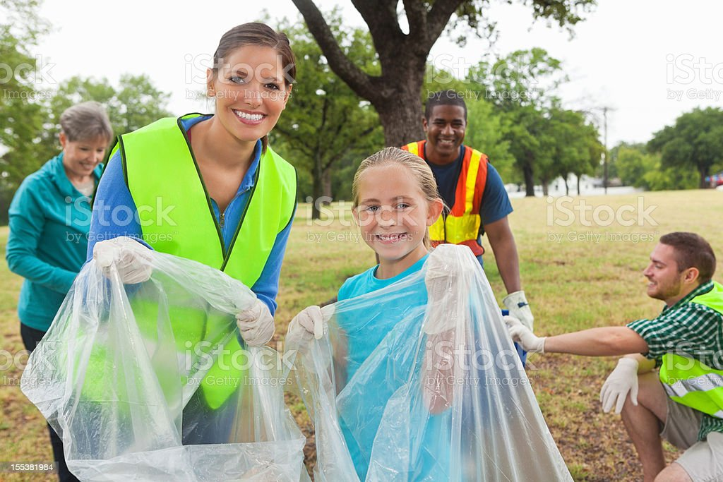 Diverse group of volunteers picking up garbage/ environmental responsibility stock photo