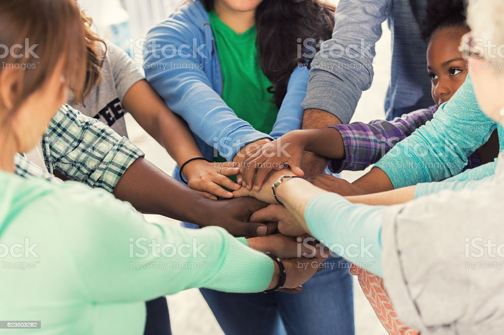 Diverse group of volunteers put hands together stock photo
