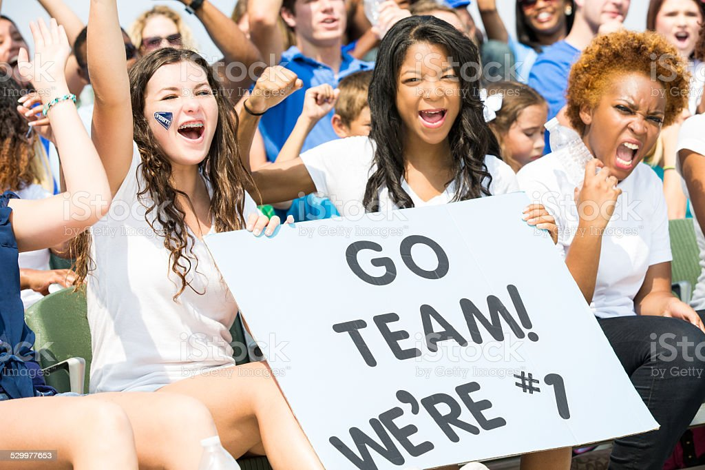 Diverse group of women cheering for sports team from bleachers