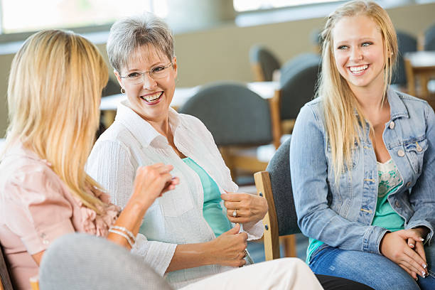 多様なグループでのお集まり、女性説明する - 学校カウンセラー ストックフォトと画像