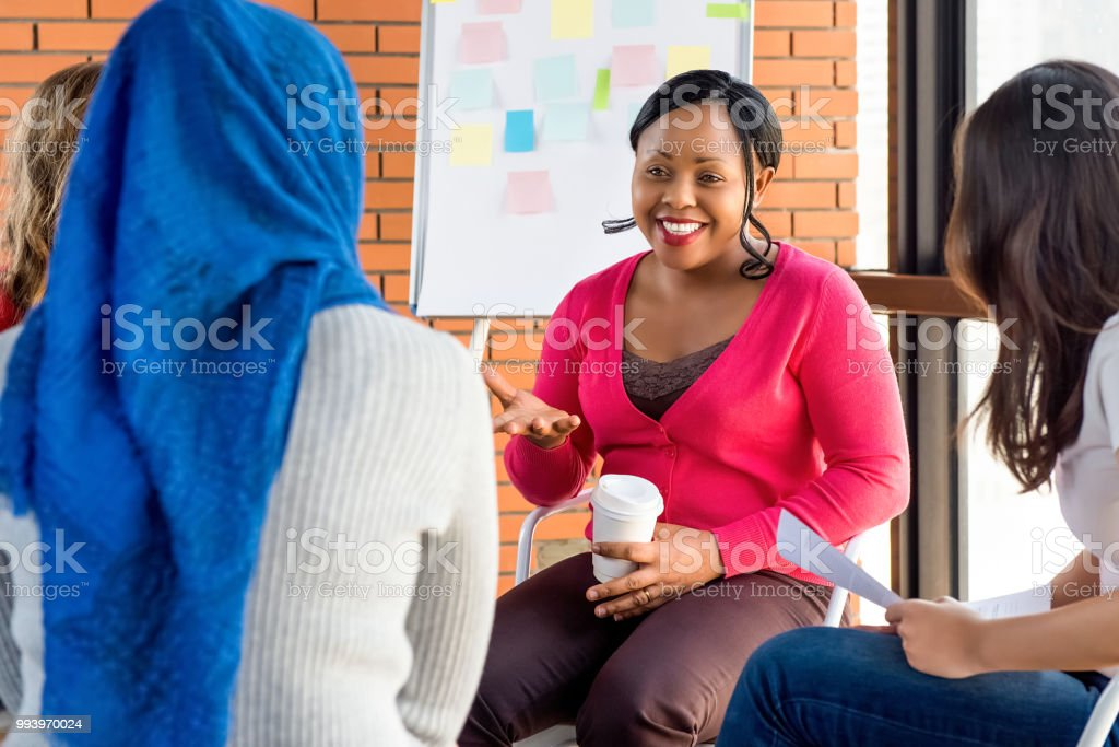 Diverse group of women in colorful clothes at the meeting stock photo