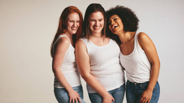 Diverse group of women laughing together Diverse group of women laughing together on white background. Females in casuals looking happy together. body positive stock pictures, royalty-free photos & images