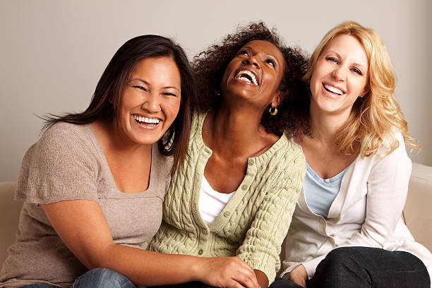 diverso grupo de mujeres riendo juntos - sólo mujeres fotografías e imágenes de stock