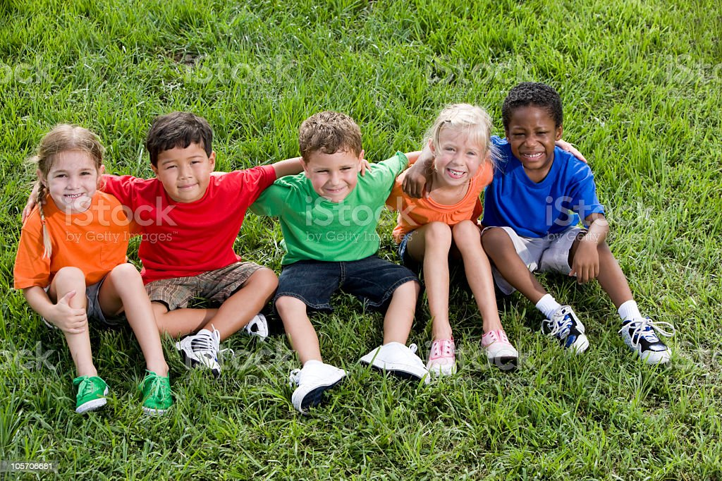 Diverse group of young children sitting in a row together royalty-free stock photo