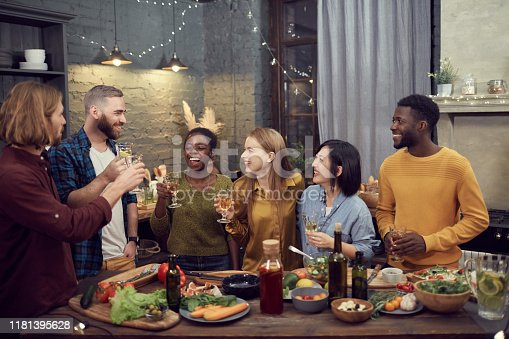 Multi-ethnic group of smiling young people enjoying dinner together standing at table in modern interior and holding wine glasses, copy space