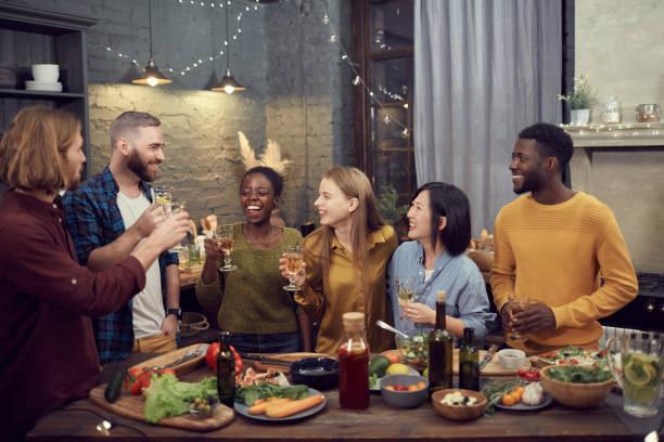 groupe diversifié de jeunes appréciant le dîner - diner entre amis photos et images de collection