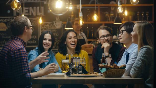 若者の多様なグループ話や冗談を言って話している、バーの楽しさがあります。彼らは、様々 なドリンクを飲みます。彼らはスタイリッシュなヒップスター設立。 ストックフォト