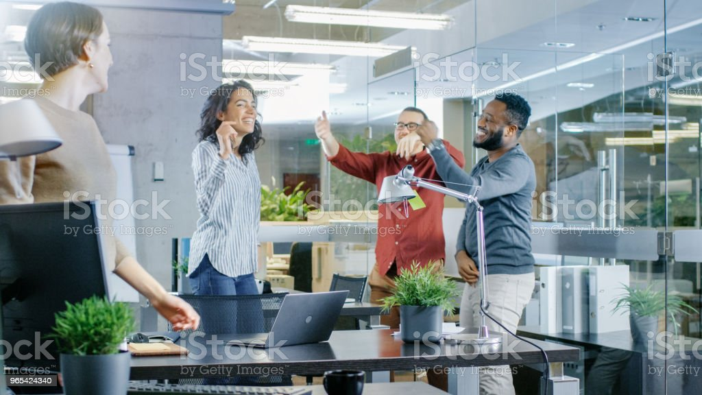 Diverse Group of Young Women and Men Dance and Have Fun in the Modern Office. Black Young Man Spins Beautiful Hispanic Woman. royalty-free stock photo
