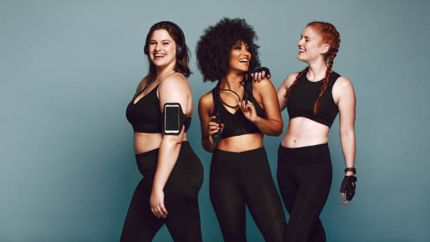 Diverse group women in sportswear after workout Multi-ethnic group of women together against grey background and smiling. Diverse group females in sportswear after workout. jacoblund stock pictures, royalty-free photos & images