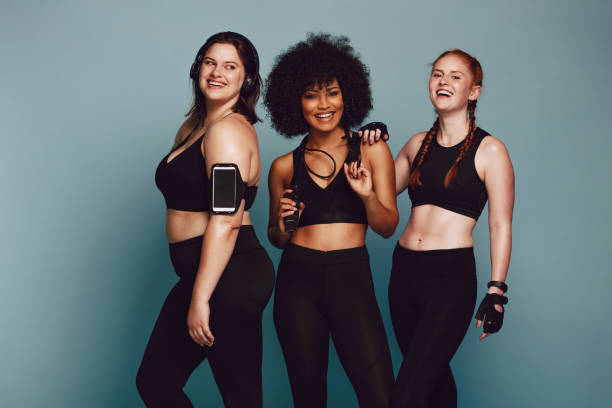 Diverse group women in sportswear Portrait of mixed race women standing together against grey background and laughing. Diverse group women in sportswear. body positive stock pictures, royalty-free photos & images