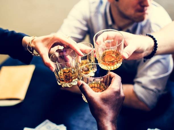 diverse hands clinking alcohol glasses - whiskey stock photos and pictures