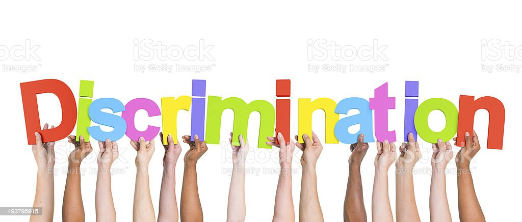 Diverse Hands Holding the Word Discrimination stock photo