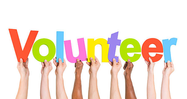 diverse hands holding the word volunteer - help single word stock photos and pictures