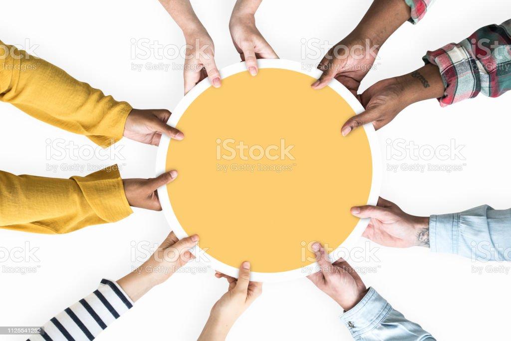 Diversas manos apoyando un amarillo en blanco redondo Junta - Foto de stock de Amarillo - Color libre de derechos