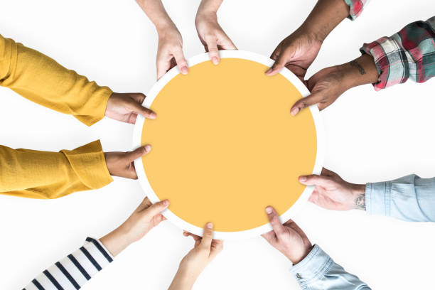 Diverse hands supporting a blank yellow round board stock photo