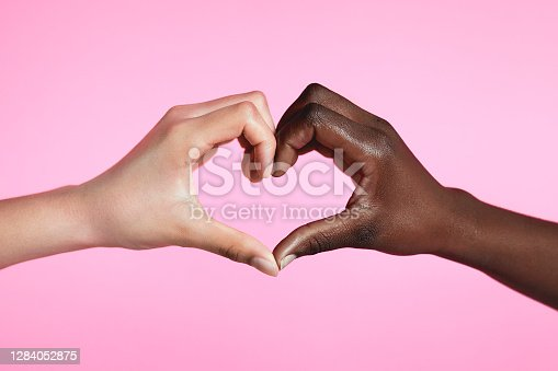 Diverse hands with love sign on pink background