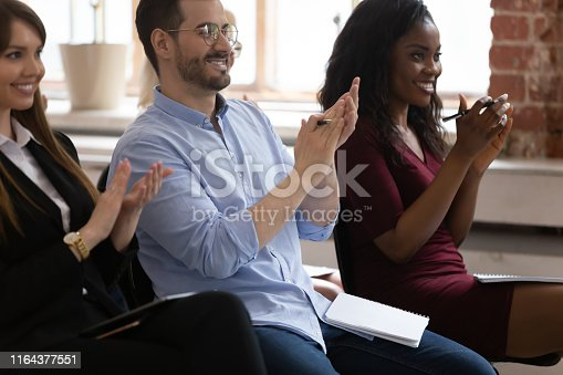 1016196912 istock photo Diverse happy business team audience group applauding sit on chairs 1164377551