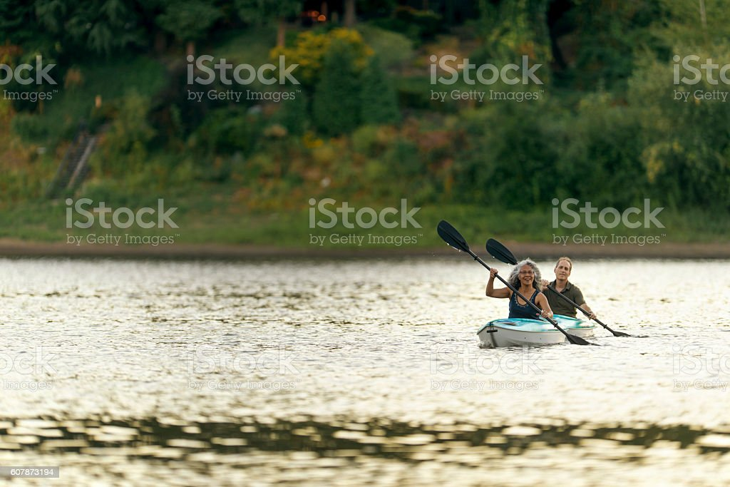 Diverse heterosexual couple paddling in their kayaks stock photo