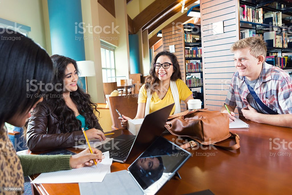 Diverse high school or college students studying together in library stock photo