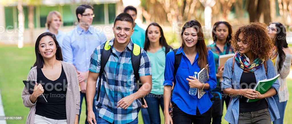 Diverse high school or college students walking on campus stock photo
