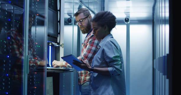 uiteenlopende it-collega's instellen van serverhardware - datacenter stockfoto's en -beelden