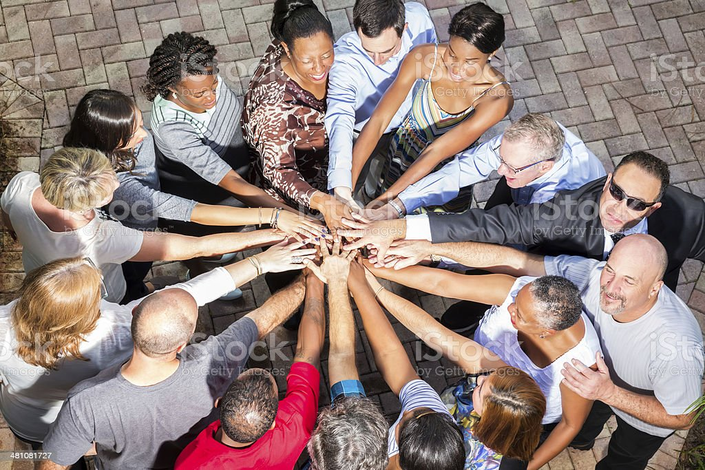 Diverse large group of people are standing in a circle with their...