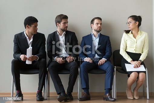 Diverse male applicants looking at female rival among men waiting for at job interview, professional career inequality, employment sexism prejudice, unfair gender discrimination at work concept