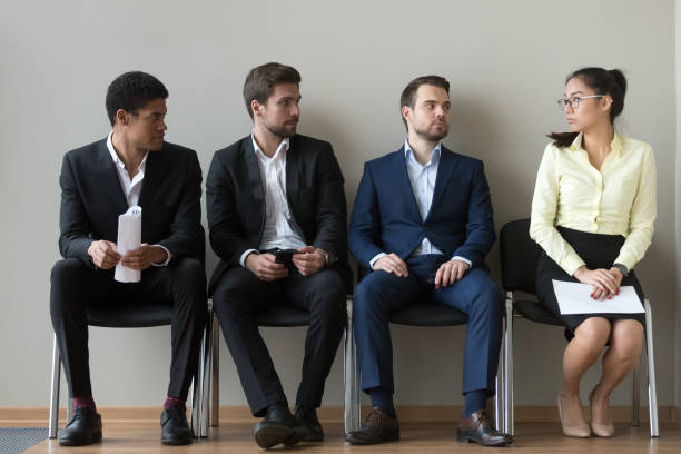 Diverse male applicants looking at female rival waiting for interview stock photo
