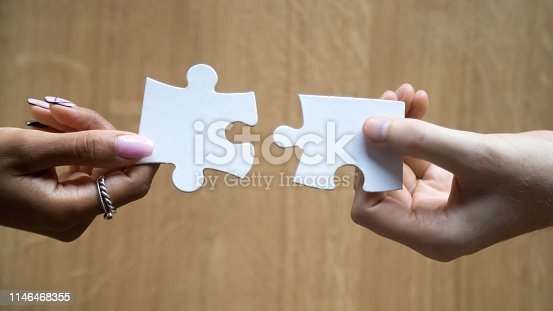 Diverse man and woman hands holding joining pieces connecting jigsaw puzzle finding best match in couple relationships concept, help in business solutions, teamwork love connection, close up top view