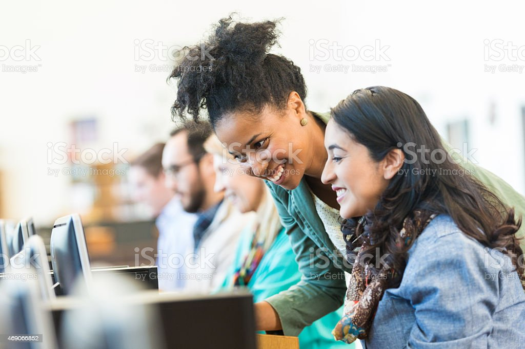 Diverse mid adult students using computers during class in college stock photo