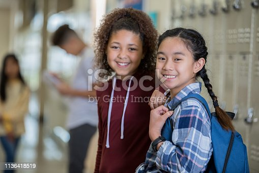 Diverse middle school girls smiling at camera in hallway near lockers before class