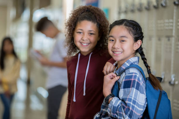 Diverse middle school girls smiling at camera in hallway near lockers before class Diverse middle school girls smiling at camera in hallway near lockers before class children only stock pictures, royalty-free photos & images