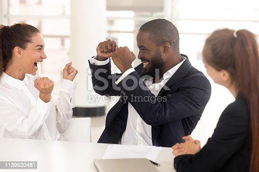 istock Diverse millennial employees celebrating at workplace startup success 1139630481