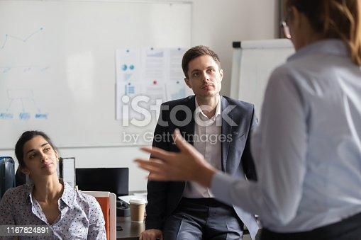 1031235468 istock photo Diverse millennial employees listening business coach at seminar 1167824891