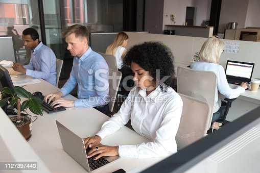 1124783373 istock photo Diverse millennial employees sitting at desk working in coworking space 1127397440