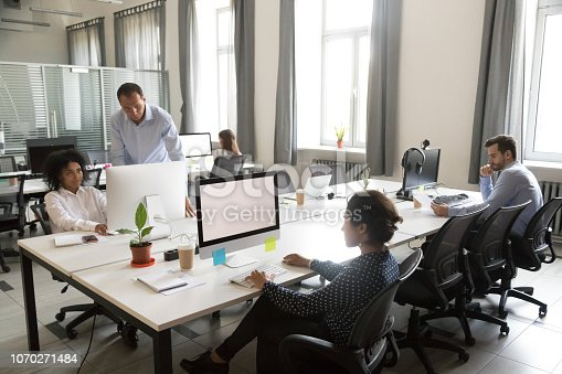 1090214584 istock photo Diverse multi-ethnic people employees working together in shared office space 1070271484