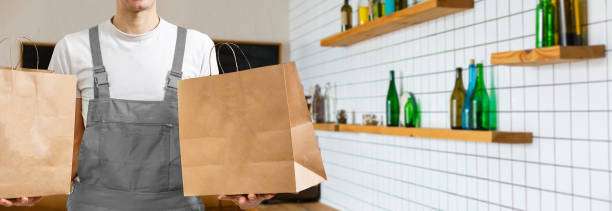 Diverse of paper containers for takeaway food. Delivery man is carrying stock photo