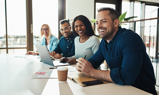 Diverse group of young businesspeople laughing while sitting together in a row at an office desk during a meeting