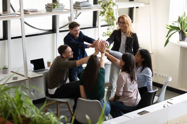 olika kontorspersonal ger höga fem firar framgång visar enighet - kulturer bildbanksfoton och bilder